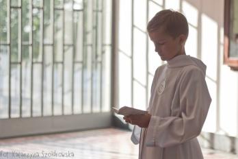 Fotografia komunijna.Chłopiec ubrany w albę czyta książeczkę do nabożeństwa. Sesja komunijna wykonana w Krakowie Mistrzejowicach ,osiedle Złotego Wieku