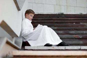 Fotografia komunijna. Chłopiec w albie siedzi na schodach przed kościołem. Plenerowa sesja komunijna w Krakowie, Nowa Huta, Mistrzejowice osiedle Złotego Wieku