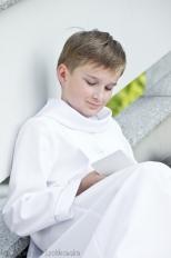 Zdjęcie komunijne. Chłopiec ubrany na biało siedzi czytając książeczkę do nabożeństwa.Sesja komunijna wykonanaprzez fotografa dziecięcego w Krakowie Prądnik Czerwony,Czyżyny