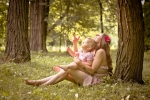 Bajkowy kadr ukazujący matkę z dzieckiem siedzące w lesie od drzewem. Roześmiana kobieta pokazuje córce magiczną gwiazdkę spadającą z nieba wprost do jej dłoni
