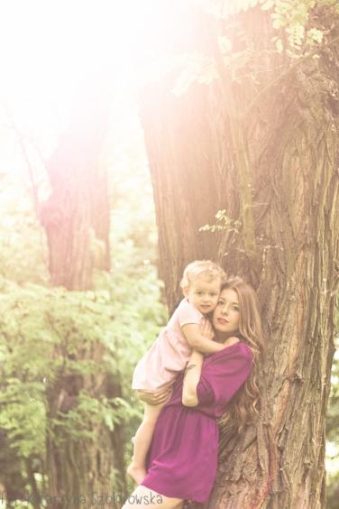 Młoda matka trzyma na rękach dziecko. Sesja rodzinna w plenerze wykonana przez fotografa w Krakowie Prądnik Czerwony, Czyżyny