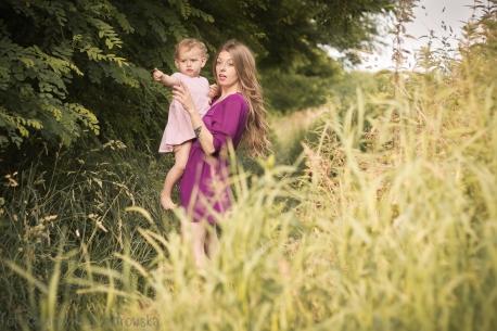 Sesja zdjęciowa matki z dzieckiem w Krakowie. Mama z córeczką na polach kwitnących ziół. Mama pokazuję dziecku cośw oddali, dziecko też wskazuje paluszkiem. Sesja dziecięca w plenerze wykonanaprzez fotografa dziecięcego w Krakowie Mistrzejowicach na osiedlu Złotego Wieku