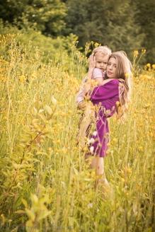 Sesja fotograficzna matki z dzieckiem w plenerze.Młoda matka przytulająca swoje dziecko stojąca pośród kwitnących kwiatów na polach w Krakowie.Rodzinna sesja w plenerze w Krakowie Prądnik Czerwony, Czyżyny