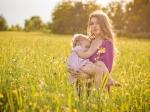 piękna karmiąca 2 letnie dziecko wśród pól