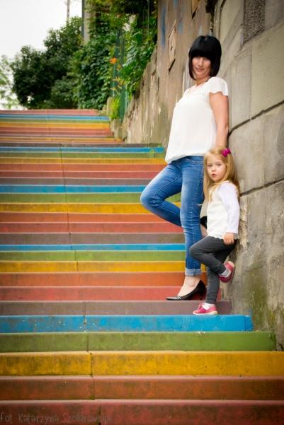 Sesja rodzinna w Krakowie Podgórzu. Czarnowłosa kobieta z córeczką pozują na kolorowych schodach w KrakowieMama i córka na kolorowych schodach w Krakowie