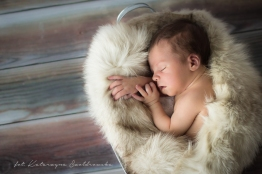 Zdjęcie niemowląt. Chłopiec, Sesja noworodkowa w Krakowie, Mistrzejowice, Złotego Wieku. Siedmiodniowy chłopczyk okryty białym futerkiem. Newborn photography Cracow