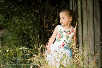 Plenerowa fotografia dziecięca w Krakowie. Jasnowłosa dziewczynka stoi przy drewnianym płotku, na tle zieleni.Sesję dziecięcą wykonano w Mistrzejowicach, Nowa Huta, osiedle Złotego Wieku