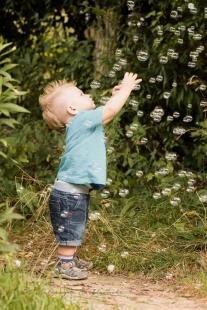 Plenerowa sesja dziecięca. Roczny chłopczyk w niebieskiej koszulce łapie bańki mydlane na tle zieleni. Sesja wykonana przezfotografa dziecięcego wKrakowie Nowej Hucie,osiedle Złotego Wieku w Nistrzejowicach