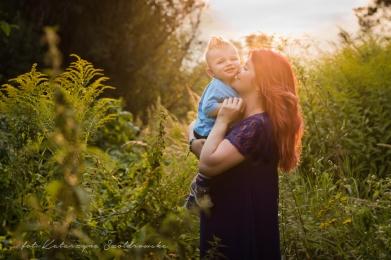 Sesja zdjęciowa matki z dzieckiem. Młoda matka całuje rocznego synka stojąc wśród traw.Fotografia dziecięca w Krakowie, sesja plenerowa