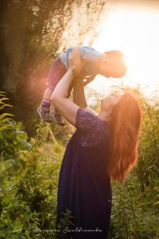 Sesja zdjęciowa matki z dzieckiem w Krakowie. Młoda matka podnosi rocznego synka do góry na tle zachodzącego słońca.Fotografia dziecięca i rodzinna w Krakowie,Nowa Huta. Złotego Wieku.Sdsja mamy z dzieckiem