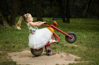 Fotografia dziecięca Kraków, Mistrzejowice,Złotego Wieku. JAsnowłosa dziewczynka na placuzabaw, buja się na motorku.