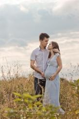 Zakochana para pozująca na polu traw do sesji ciazowej wykonanej w Krakowie Mistrzejowice Nowa Huta , Prądnik.Maternity photography Cracow